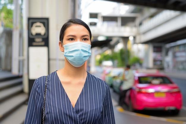 Junge asiatische geschäftsfrau mit maske, die an der taxistation in den stadtstraßen wartet