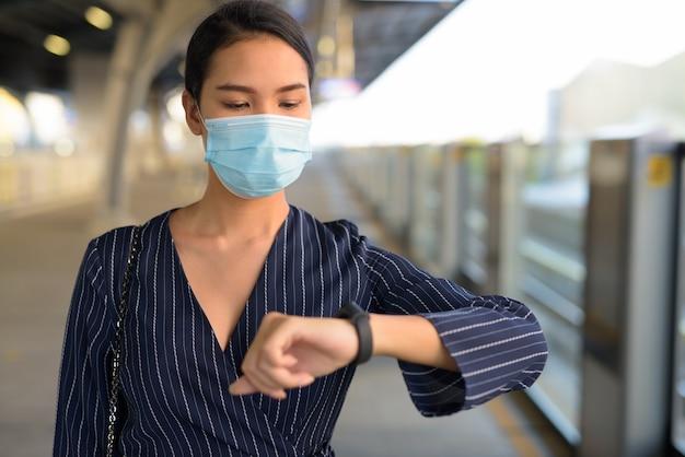 Junge asiatische geschäftsfrau mit maske, die die zeit an der skytrain-station wartet und prüft