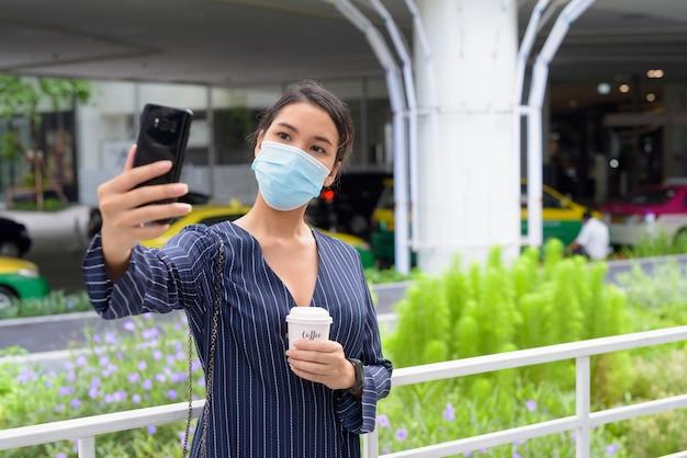 Junge asiatische geschäftsfrau mit maske, die selfie nimmt, während kaffee unterwegs als die neue normalität in der stadt draußen trinkt