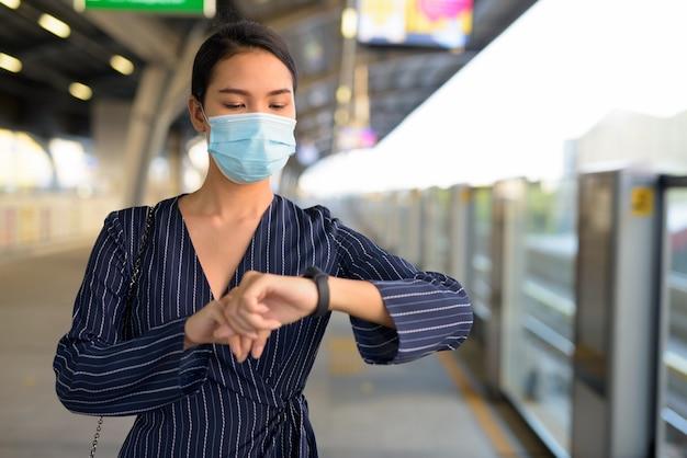 Junge asiatische geschäftsfrau mit maske, die smartwatch an der skytrain-station wartet und prüft
