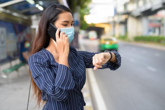 Junge asiatische geschäftsfrau mit maske, die smartwatch prüft und am telefon an der bushaltestelle spricht