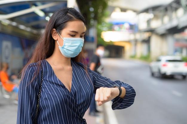Junge asiatische geschäftsfrau mit maske, die smartwatch prüft und an der bushaltestelle wartet