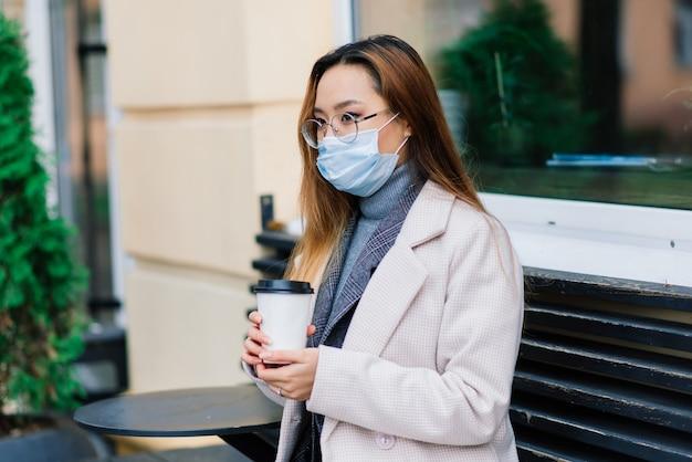 Junge asiatische geschäftsfrau mit maske, die telefon benutzt und mit abstand vor dem café sitzt?