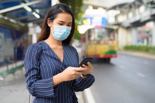 Junge asiatische geschäftsfrau mit maske unter verwendung des telefons an der bushaltestelle