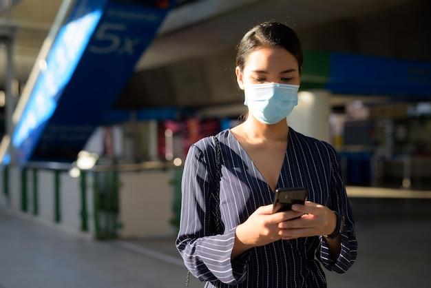 Junge asiatische geschäftsfrau mit maske unter verwendung des telefons beim gehen vom bahnhof weg