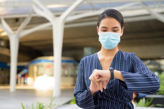 Junge asiatische geschäftsfrau mit maske zum schutz vor dem ausbruch des koronavirus, der die zeit in der stadt prüft