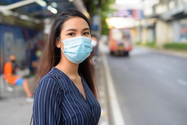 Junge asiatische geschäftsfrau mit maske zum schutz vor dem ausbruch des koronavirus, die an der bushaltestelle wartet