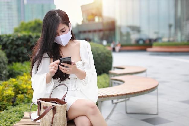 Junge asiatische geschäftsfrau mit schutzmaske, die öffentlich im freien sitzt und am smartphone arbeitet