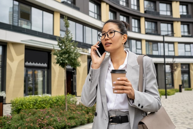 Junge asiatische geschäftsfrau mit smartphone nach gehör und getränk in der hand