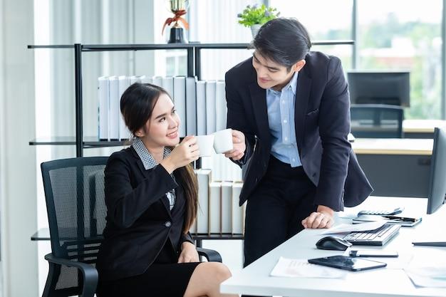 Junge asiatische geschäftsfrau und geschäftsleute, während sie zusammenarbeiten und sich entspannen und eine tasse kaffee vor der arbeit halten, geschäftstreffen mit computer auf holztischhintergrund im büro