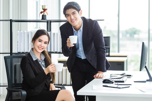 Junge asiatische geschäftsfrau und geschäftsmannpartner beim zusammenarbeiten und entspannen, die eine tasse kaffee in vor geschäftstreffen mit computer auf holztisch halten