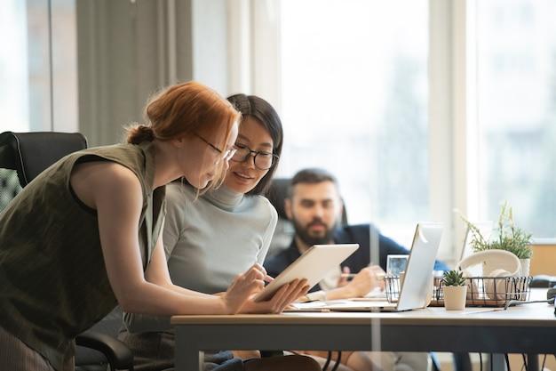 Junge asiatische geschäftsfrau und ihr kaukasischer kollege betrachten anzeige des touchpads, während sie sich über berichtspunkte beraten