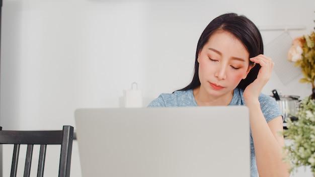 Junge asiatische geschäftsfrauaufzeichnungen des einkommens und der ausgaben zu hause. dame sorgte sich, ernst, druck bei der anwendung des laptopaufzeichnungsbudgets, der steuer, des finanzdokuments, das in der modernen küche am haus arbeitet.