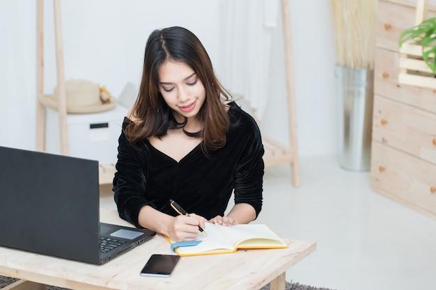 Junge asiatische geschäftsfrauen, die mit computer-laptop arbeiten und werbung auf notizbuch in ihrem geschäftsladen schreiben?