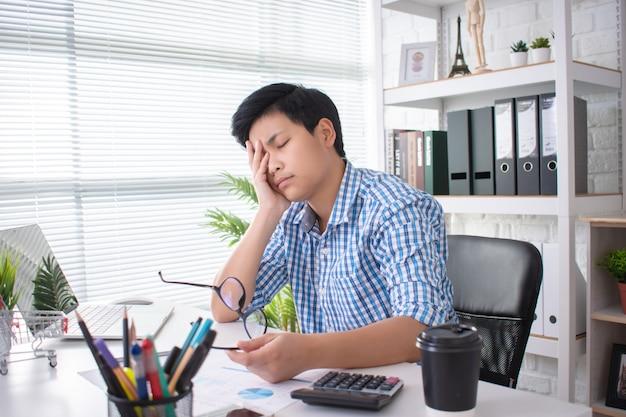 Junge asiatische geschäftsleute haben kopfschmerzen durch harte arbeit
