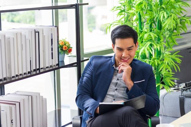 Junge asiatische geschäftsmänner, die den terminkalender im büro aufpassen