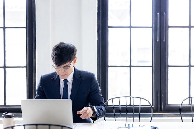 Junge asiatische geschäftsmann mit laptop-computer arbeiten und videokonferenz treffen, junge asiatische kreative mann suchen computer-laptop.
