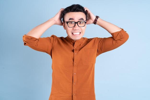 Junge asiatische geschäftsmann posiert auf blauem hintergrund