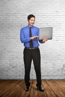 Junge asiatische geschäftsmannstellung beim schreiben auf laptop