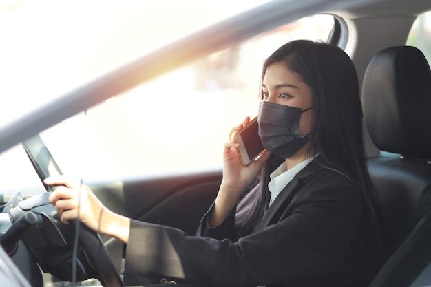 Junge asiatische gesunde frau im schwarzen anzug mit schutzmaske für das gesundheitswesen im automobil und mit smartphone und auto. neues normales und soziales distanzierungskonzept