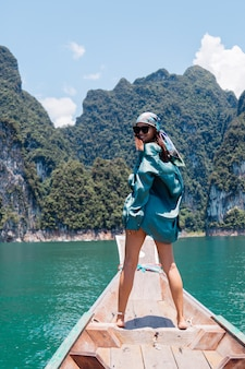 Junge asiatische glückliche frau blogger-tourist in seidenanzug und schal und sonnenbrille im urlaub reisen um thailand auf asiatischem boot, khao sok nationalpark.