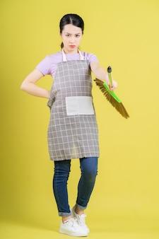 Junge asiatische hausfrau posiert auf gelbem hintergrund