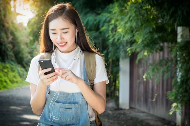Junge asiatische hipster tragen kopfhörer musik hören durch smartphone stehen im freien auf natur hintergrund