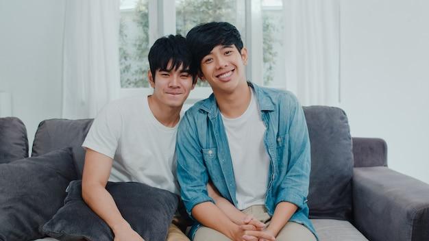 Junge asiatische homosexuelle paare des porträts, die glücklich sich fühlen, zu hause zu lächeln. asiatische lgbtq-männer entspannen sich das toothy lächeln, das zur kamera beim morgens liegen auf sofa im wohnzimmer schaut.
