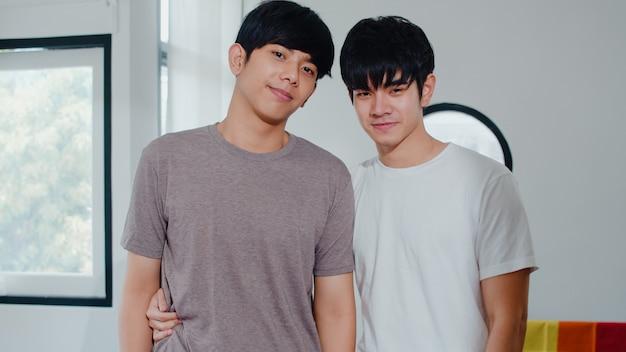 Junge asiatische homosexuelle paare des porträts, die glücklich sich fühlen, zu hause zu lächeln. asiatische lgbtq-männer entspannen sich das toothy lächeln, das zur kamera schaut, während sie im wohnzimmer zu hause morgens umarmen.