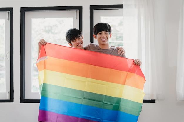 Junge asiatische homosexuelle paare des porträts, die glücklich sind, regenbogenflagge zu hause zeigend. asien lgbtq + männer entspannen sich das toothy lächeln, das zur kamera schaut, während sie im modernen wohnzimmer haus morgens umarmen.