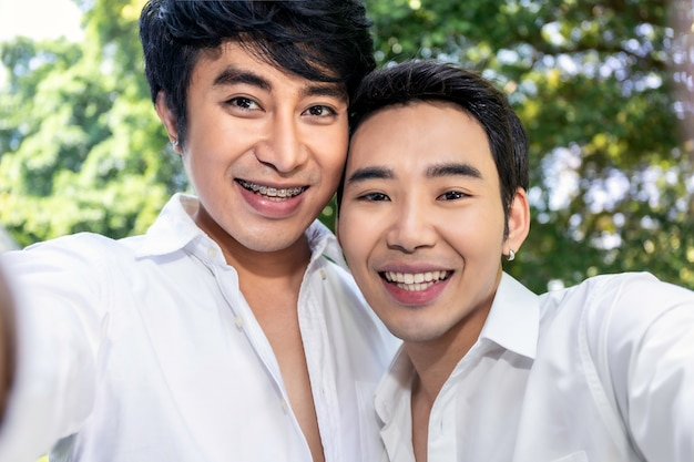 Junge asiatische homosexuelle paare, die selbstporträt mit intelligentem telefon nehmen
