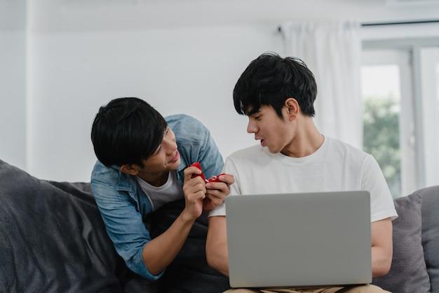 Junge asiatische homosexuelle paare schlagen am modernen haus vor, das glückliche lächeln der jugendlich koreanischen lgbtq-männer haben romantische zeit, während das vorschlagen und die heirat überraschen abnutzungsehering im wohnzimmer am haus.