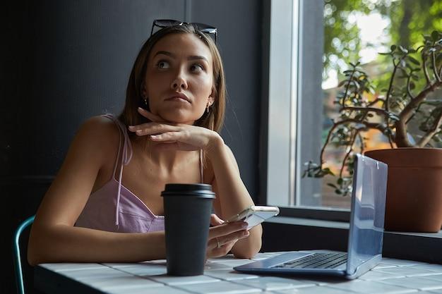 Junge asiatische hübsche frau sitzt am tisch des cafés mit laptop mit smartphone