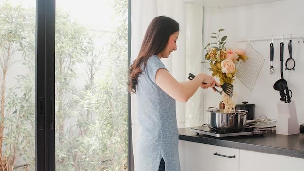 Junge asiatische japanische dame genießen, zu hause zu kochen. lebensstilfrauen glücklich, das lebensmittel zubereitend, das morgens teigwaren und spaghettis zum frühstücksmahlzeit in der modernen küche am haus macht.
