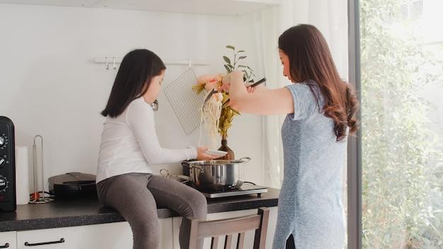 Junge asiatische japanische mutter und tochter, die zu hause kocht. lebensstilfrauen glücklich, teigwaren und spaghettis zum frühstücksmahlzeit in der modernen küche am haus morgens zusammen zu machen.