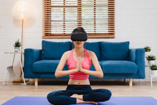 Junge asiatische jugendlichfrau, die simulator der virtuellen realität beim üben von yoga im wohnzimmer verwendet