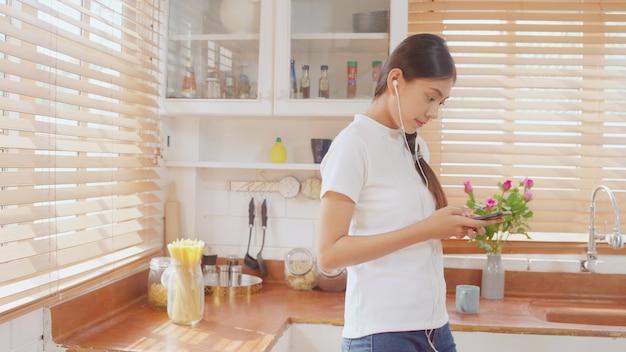 Junge asiatische jugendlichfrau, die warmen kaffee unter verwendung der hörenden musik des smartphone trinkt und soziales überprüft