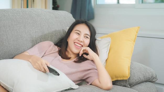 Junge asiatische jugendlichfrau, die zu hause, weibliches glaubendes glückliches lügen auf sofa im wohnzimmer fernsieht. lebensstilfrau entspannen sich am konzept des morgens zu hause.