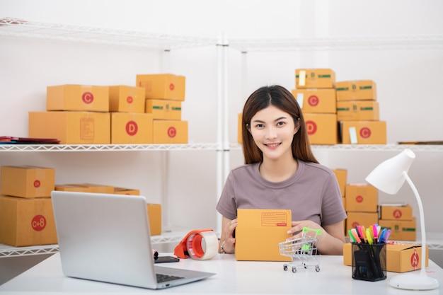 Junge asiatische jugendlichigentümergeschäftsfrau arbeiten zu hause für das on-line-einkaufen