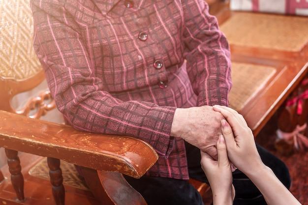Junge asiatische junge mädchenbetreuerin, die oma hände hält, konzept der hilfe für das ältere leben mit dunklem hintergrund, nahaufnahme, kopienraum, beschnittene ansicht