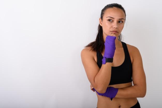 Junge asiatische kämpferin, die mit boxpackungen gegen leerraum denkt und auf distanz schaut