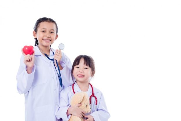 Junge asiatische kinder täuschen vor, doktor zu sein, der über weißem hintergrund steht