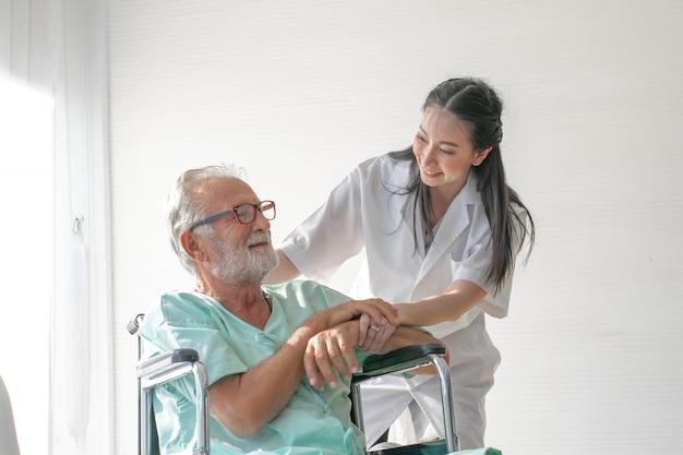 Junge asiatische krankenschwester, die mit dem patienten des alten mannes im rollstuhl spricht