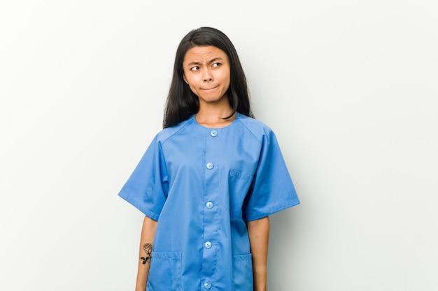 Junge asiatische krankenschwester frau verwirrt, fühlt sich zweifelhaft und unsicher.