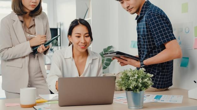 Junge asiatische kreative geschäftsmann und geschäftsfrau chef manager gespräch erklären projektbericht auf laptop