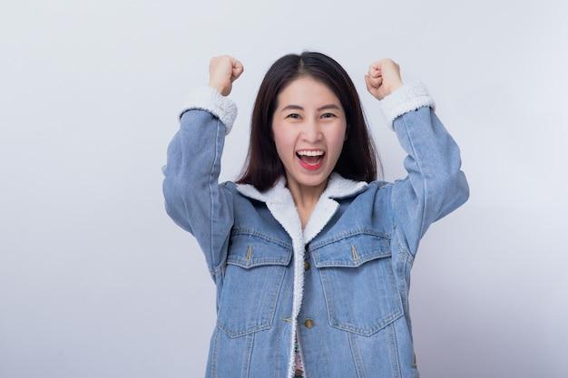 Junge asiatische lächelnde aufgeregte frau, die ihre hand mit dem ausdruck sich überrascht und überrascht fühlt zeigt