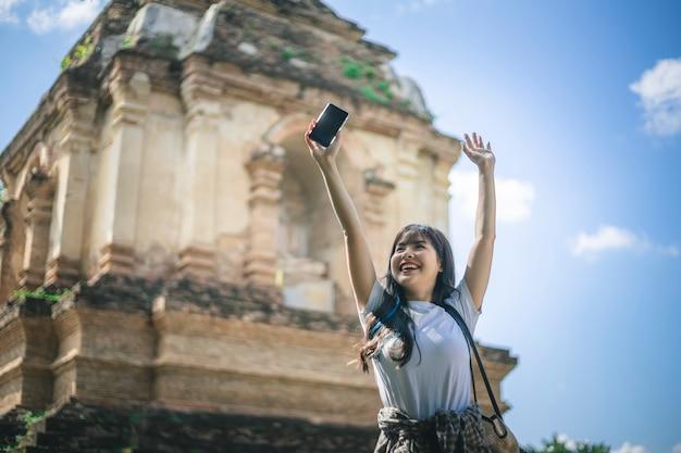 Junge asiatische lächelnde reisendfrau beim reisen um thailändischen alten tempel