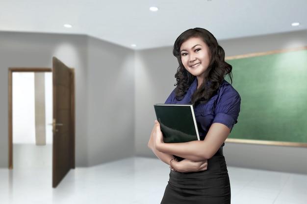 Junge asiatische lehrerfrau mit buch in ihrer hand