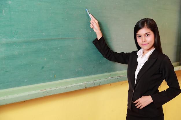 Junge asiatische lehrerin, die etwas auf altem grünem brett zeigt