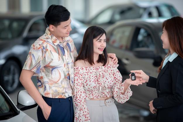 Junge asiatische liebhaber kaufen gerne beim händler ein neues auto und beim autohändler ein auto.